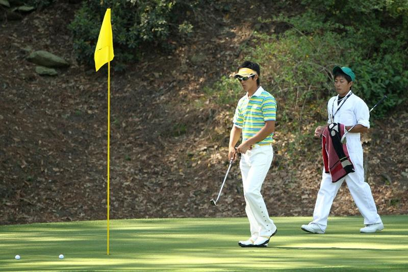 AUGUSTA, GA - APRIL 06:  Ryo Ishikawa of Japan walks across a green alongside his caddie during a practice round prior to the 2010 Masters Tournament at Augusta National Golf Club on April 6, 2010 in Augusta, Georgia.  (Photo by Andrew Redington/Getty Images)