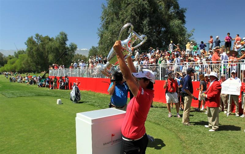 RANCHO MIRAGE, CA - APRIL 03:  Yani Tseng of Taiwan plays walks onto the 1st tee and raises the trophy she won last year at the start of her final round in the 2011 Kraft Nabisco Championship on the Dinah Shore Championship Course at the Mission Hills Country Club on April 3, 2011 in Rancho Mirage, California.  (Photo by David Cannon/Getty Images)
