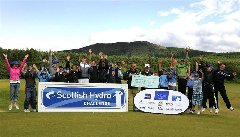INVERNESS, SCOTLAND - AUGUST 01: Children are pictured together with Paul Lawrie (R) and Liam Barn (L) who gives a cheque to Paul Lawrie Foundation during the Scottish Hydro Challenge at the Macdonald Spey Valley Golf Course on August 01, 2009 in Inverness, Scotland. (Photo by Tom Dulat/Getty Images)