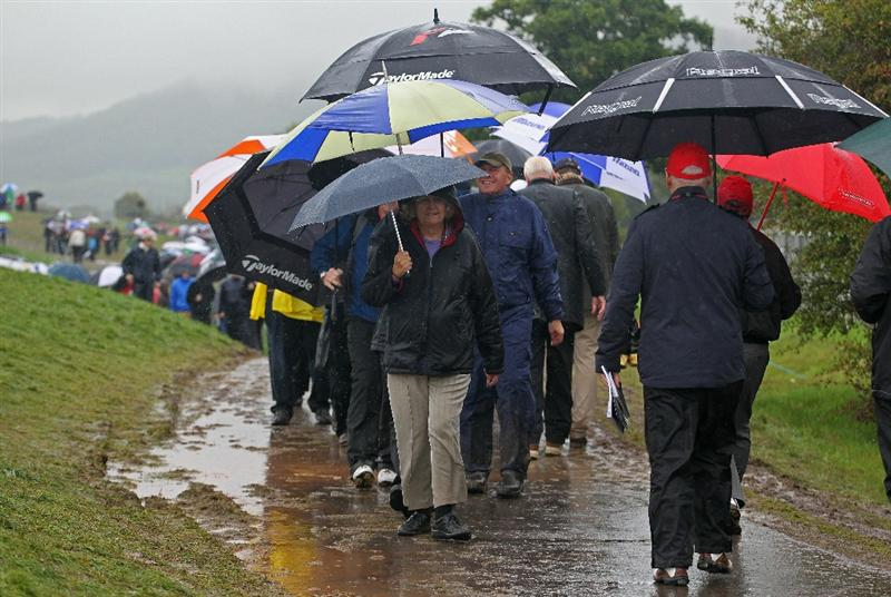 NEWPORT, WALES - OCTOBER 01:  Spectators walk with umbrellas as rain falls and play is suspended during the Morning Fourball Matches during the 2010 Ryder Cup at the Celtic Manor Resort on October 1, 2010 in Newport, Wales.  (Photo by Andy Lyons/Getty Images)