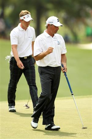 AUGUSTA, GA - APRIL 08:  Fred Couples celebrates on the 17th hole as Luke Donald of England walks behind him during the second round of the 2011 Masters Tournament at Augusta National Golf Club on April 8, 2011 in Augusta, Georgia.  (Photo by Jamie Squire/Getty Images)