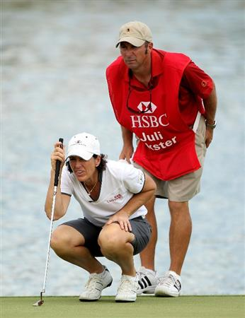 SINGAPORE - FEBRUARY 26:  Juli Inkster of the USA and her caddie line up a putt on the 18th hole during the second round of the HSBC Women's Champions at the Tanah Merah Country Club on February 26, 2010 in Singapore.  (Photo by Andrew Redington/Getty Images)