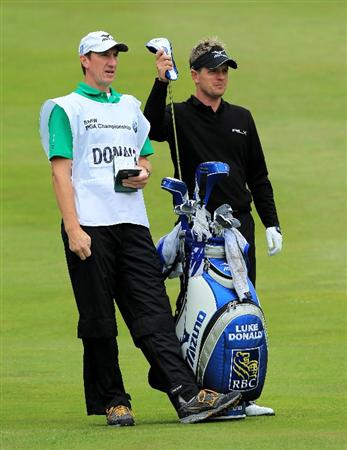 VIRGINIA WATER, ENGLAND - MAY 28:  Luke Donald of England  lines up a shot with caddie John McClaren during the third round of the BMW PGA Championship at the Wentworth Club on May 28, 2011 in Virginia Water, England.  (Photo by David Cannon/Getty Images)
