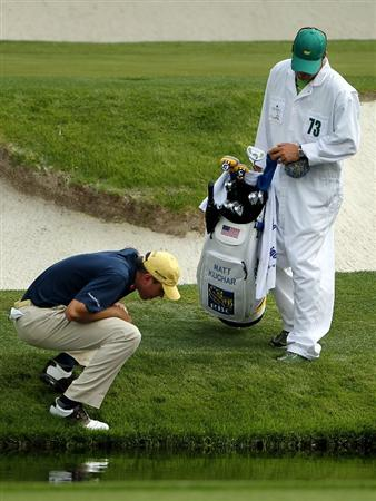 AUGUSTA, GA - APRIL 08:  Matt Kuchar inspects his lie on the 12th hole as his caddie Lance Bennett look on during the second round of the 2011 Masters Tournament at Augusta National Golf Club on April 8, 2011 in Augusta, Georgia.  (Photo by Jamie Squire/Getty Images)
