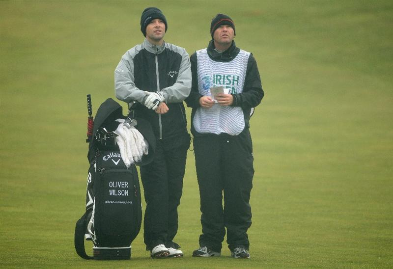 BALTRAY, IRELAND - MAY 15:  Oliver Wilson of England waits with his caddie Richard Hill on the third hole during the second round of The 3 Irish Open at County Louth Golf Club on May 15, 2009 in Baltray, Ireland.  (Photo by Andrew Redington/Getty Images)