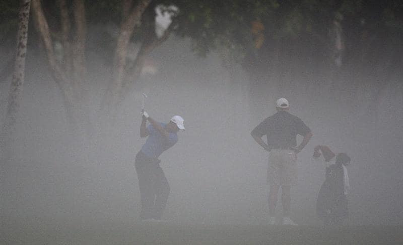 DORAL, FL - MARCH 11:  Tiger Woods of the USA plays his second shot in the early morning mist as his caddie Steve Williams of New Zealand  watches during the final day of practice for the World Golf Championships-CA Championship at the Doral Golf Resort & Spa on March 11, 2009 in Miami, Florida  (Photo by David Cannon/Getty Images)