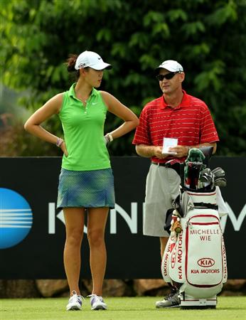 KUALA LUMPUR, MALAYSIA - OCTOBER  21:  Michelle Wie of USA speaks to her caddie on the 10th hole during the Sime Darby Pro-Am at the KLGCC Golf Course on October 21, 2010 in Kuala Lumpur, Malaysia.  (Photo by Stanley Chou/Getty Images)