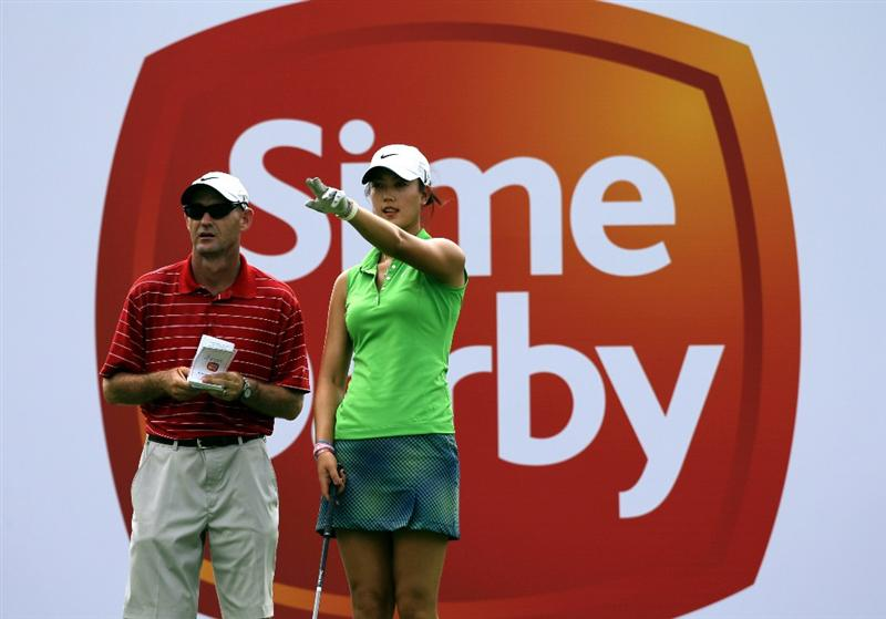 KUALA LUMPUR, MALAYSIA - OCTOBER 21:  Michelle Wie of USA speaks to her caddie on the 9th hole during the Sime Darby Pro-Am at the KLGCC Golf Course on October 21, 2010 in Kuala Lumpur, Malaysia.  (Photo by Stanley Chou/Getty Images)