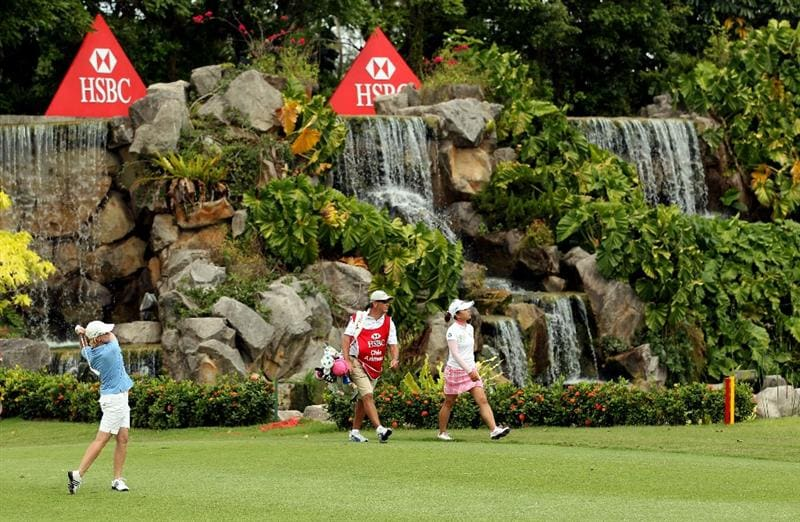 SINGAPORE - FEBRUARY 27:  Karrie Webb of Australia hits her second shot on the 18th hole as Chie Arimura of Japan and her caddie look on during the final round of the HSBC Women's Champions at the Tanah Merah Country Club on February 27, 2011 in Singapore.  (Photo by Andrew Redington/Getty Images)