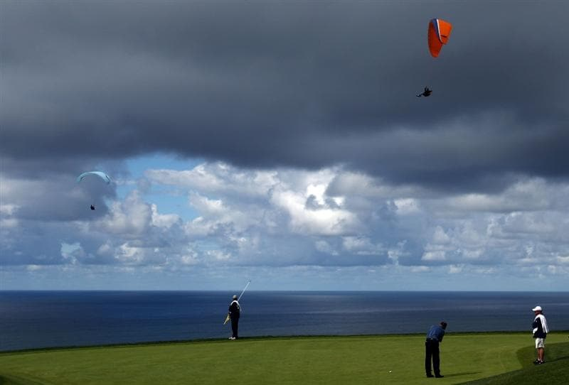 LA JOLLA, CA - FEBRUARY 08:  Gregor Main putts on the 4th green as Dustin Johnson and Ricky Barnes look on with paragliders flying overhead during the Final Round of the Buick Invitational at the Torrey Pines North Course on February 8, 2009 in La Jolla, California. (Photo by Donald Miralle/Getty Images)