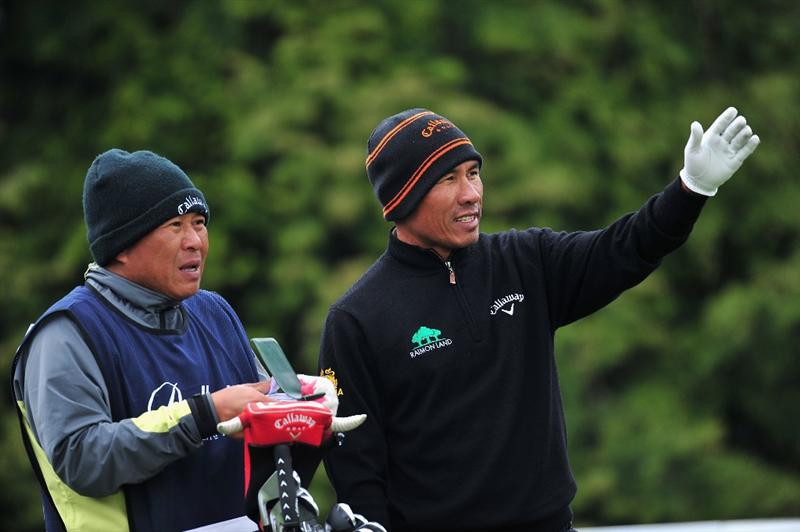 JEJU, SOUTH KOREA - APRIL 25:  Thongchai Jaidee of Thailand and caddie discuss a shot during the third round of the Ballantine's Championship at Pinx Golf Club on April 25, 2009 in Jeju, South Korea.  (Photo by Stuart Franklin/Getty Images)