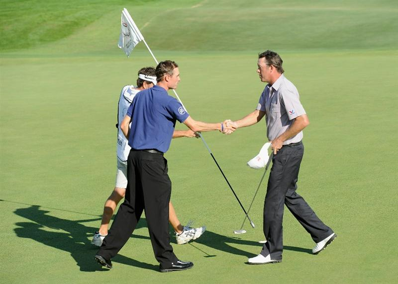 VILAMOURA, PORTUGAL - OCTOBER 17:  Richard Green of Australia is congraulated by playing partner  Rhys Davies of Wales on the 18th hole during the final round of the Portugal Masters at the Oceanico Victoria Golf Course on October 17, 2010 in Vilamoura, Portugal.  (Photo by Stuart Franklin/Getty Images)