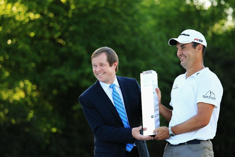 VIRGINIA WATER, ENGLAND - MAY 23:  Simon Khan (R) of England accepts the trophy from European Tour Chief Executive George O'Grady following his victory in the BMW PGA Championship on the West Course at Wentworth on May 23, 2010 in Virginia Water, England.  (Photo by Warren Little/Getty Images)