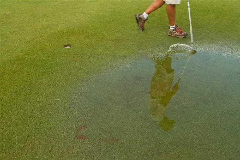SPRINGFIELD, IL - JUNE 13: A caddie drags a club through a puddle on the practice putting green during a weather delay in the fourth round of the LPGA State Farm Classic at Panther Creek Country Club on June 13, 2010 in Springfield, Illinois. (Photo by Darren Carroll/Getty Images)