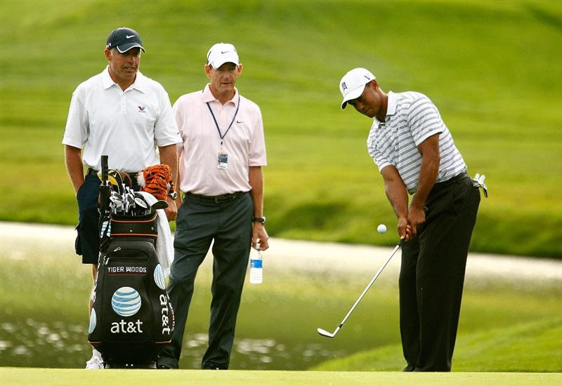 CHASKA, MN - AUGUST 10:  Tiger Woods (R) hits a shot as his caddie Steve Williams (L) and his coach Hank Haney look on during a practice round prior to the start of the 91st PGA Championship at the Hazeltine Golf Club on August 10, 2009 in Chaska, Minnesota.  (Photo by Scott Halleran/Getty Images)