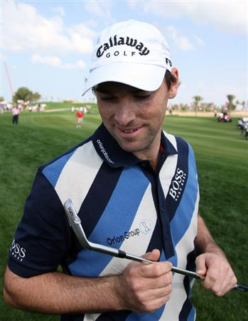 ABU DHABI, UNITED ARAB EMIRATES - JANUARY 16:  Oliver Wilson of England inspects the damage to his nine iron after he had damaged it hitting from the rocks at the third hole during the second round of the Abu Dhabi Golf Championship held at the Abu Dhabi Golf Club on January 16, 2009 in Abu Dhabi, United Arab Emirates  (Photo by David Cannon/Getty Images)