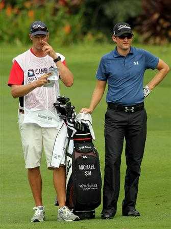 KUALA LUMPUR, MALAYSIA - OCTOBER 29: Michael Sim of Australia and his caddie waits on the 1st hole during day two of the CIMB Asia Pacific Classic at The MINES Resort & Golf Club on October 29, 2010 in Kuala Lumpur, Malaysia.  (Photo by Stanley Chou/Getty Images)