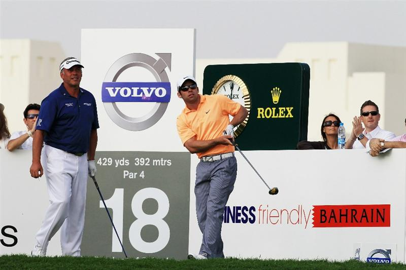 BAHRAIN, BAHRAIN - JANUARY 29:  Paul Casey of England drives at the 18th hole watched by his playing partner Darren Clarke of Northern Ireland during the third round of the 2011 Volvo Champions held at the Royal Golf Club on January 29, 2011 in Bahrain, Bahrain.  (Photo by David Cannon/Getty Images)