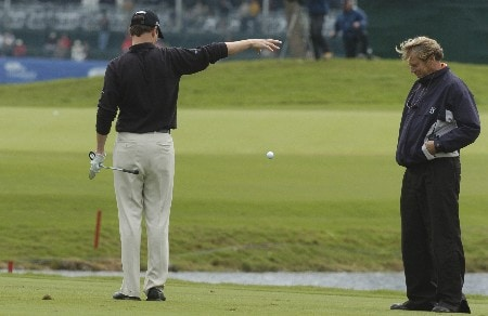 Zach Johnson drops a ball on the eighth hole as PGA rules official John Brendle watches during  second-round competition March 4, 2005  at the Ford Championship at Doral in Miami.