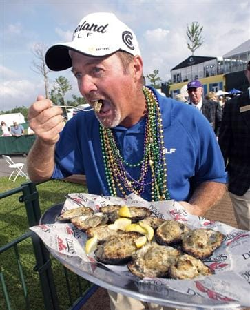 AVONDALE, LA - APRIL 26: Zurich Classic winner Jerry Kelly eats a charbroiled oyster from a tray as he makes his way to the interview room after his win during the final round of the Zurich Classic at TPC Louisiana on April 26, 2009  in Avondale, Louisiana. (Photo by Dave Martin/Getty Images)