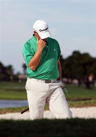 MIAMI - OCTOBER 18:  Justin Smith reacts after blading the ball accross the green and into a trap on the 18th hole during the final round of the 2009 Nationwide Tour Miccosukee Championship at the Miccosukee Golf & Country Club on October 18, 2009 in Miami, Florida.  (Photo by Doug Benc/Getty Images)