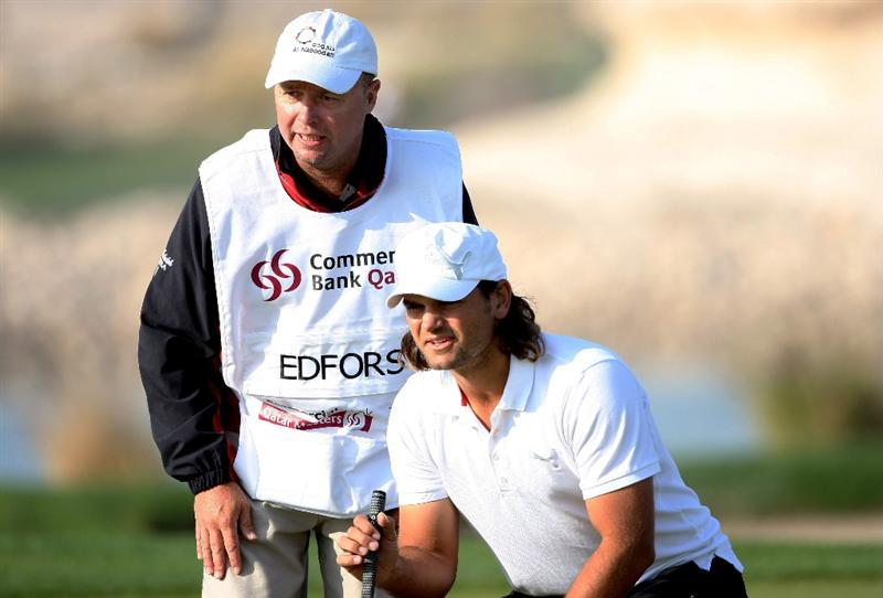 DOHA, QATAR - JANUARY 22:  Johan Edfors of Sweden lines up a putt with his caddie on the 15th hole during the first round of  the Commercialbank Qatar Masters at Doha Golf Club on January 22, 2009 in Doha, Qatar.  (Photo by Andrew Redington/Getty Images)