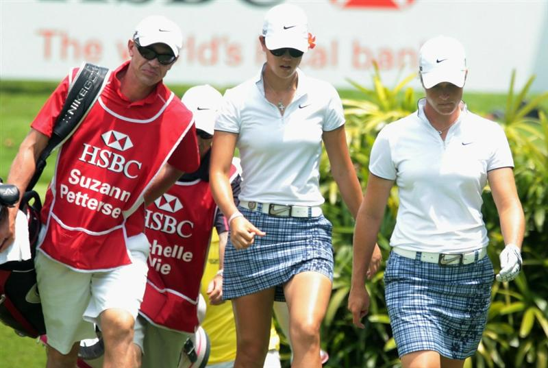 SINGAPORE - FEBRUARY 25:  Michelle Wie of the USA (L) and Suzann Pettersen of Norway walk with their caddies during the second round of the HSBC Women's Champions 2011 at the Tanah Merah Country Club on February 25, 2011 in Singapore, Singapore.  (Photo by Scott Halleran/Getty Images)