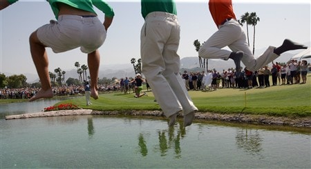 RANCHO MIRAGE, CA - APRIL 06:  Lorena Ochoa of Mexico (just to the left of the centre pair of legs) leads the traditional rush to the water beside the 18th green as the legs of her caddie and family friends appear from the wall on the bridge to the green after the final round of the Kraft Nabisco Championship at the Mission Hills Country Club, on April 6, 2008 in Rancho Mirage, California.  (Photo by David Cannon/Getty Images)