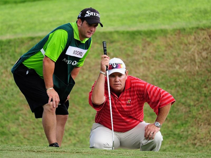 EAST LONDON, SOUTH AFRICA - JANUARY 07:  Titch Moore of South Africa and caddie line up his putt on the 17th hole during the first round of the Africa Open at the East London Golf Club on January 7, 2010 in East London, South Africa.  (Photo by Stuart Franklin/Getty Images)
