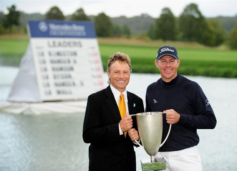 COLOGNE, GERMANY - SEPTEMBER 13:  James Kingston of South Africa is presented with the winners trophy by Bernhard Langer of Germany after winning the playoff against Ander Hansen of Denmark during the final round of the Mercedes-Benz Championship at the Gut Larchenhof Golf Club on September 13, 2009 in Cologne, Germany.  (Photo by Stuart Franklin/Getty Images)