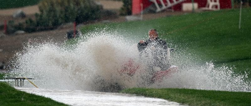 ABU DHABI, UNITED ARAB EMIRATES - JANUARY 15:  An official races his cart through standing water  on his way to pick up players waiting out a hail storm that led to play being suspended during the first round of the Abu Dhabi Golf Championship held at the Abu Dhabi Golf Club on January 15, 2009 in Abu Dhabi, United Arab Emirates  (Photo by David Cannon/Getty Images)