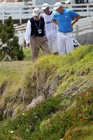PEBBLE BEACH, CA - JUNE 20:  Dustin Johnson and his caddie Bobby Brown look into a hazard on the fourth hole alongside a USGA rules official during the final round of the 110th U.S. Open at Pebble Beach Golf Links on June 20, 2010 in Pebble Beach, California.  (Photo by Jeff Gross/Getty Images)