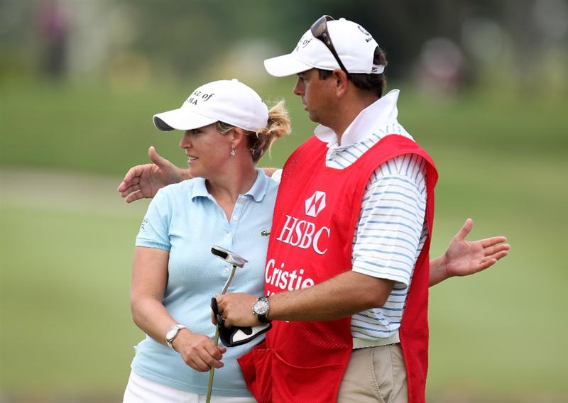 SINGAPORE - FEBRUARY 25:  Cristie Kerr of the USA with her caddie on the 18th green during the first round of the HSBC Women's Champions at the Tanah Merah Country Club on February 25, 2010 in Singapore.  (Photo by Ross Kinnaird/Getty Images)