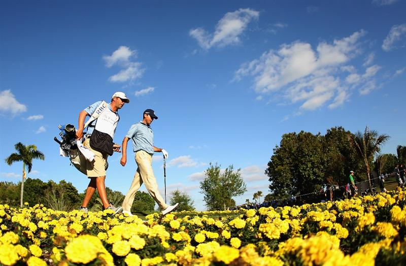 DORAL, FL - MARCH 13:  Matt Kuchar walks off the 15th tee with his caddie Lance Bennett during the final round of the 2011 WGC- Cadillac Championship at the TPC Blue Monster at the Doral Golf Resort and Spa on March 13, 2011 in Doral, Florida.  (Photo by Mike Ehrmann/Getty Images)