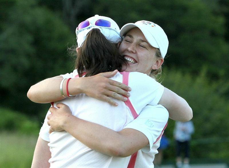 MANCHESTER, MA - JUNE 11:  Lisa Maguire of Great Britain and Ireland is hugged by teammate Sally Watson after Maguire sunk a putt on the 18th green in Four-Balls  competition to earn a point over the United Statest during the 2010 Curtis Cup Match at the Essex Country Club on June 11, 2010 in Manchester, Massachusetts. (Photo by Jim Rogash/Getty Images)