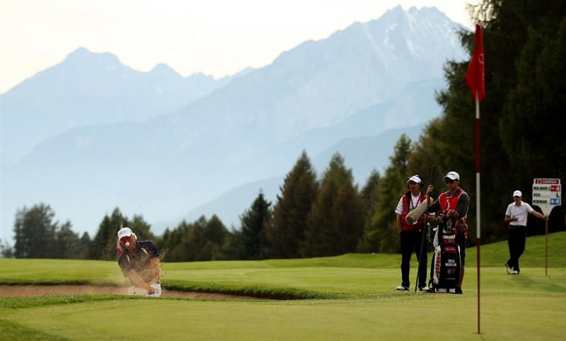 CRANS, SWITZERLAND - SEPTEMBER 02:  Greg Norman of Australia plays out of the 15th greenside bunker during the first round of The Omega European Masters at Crans-Sur-Sierre Golf Club on September 2, 2010 in Crans Montana, Switzerland.  (Photo by Warren Little/Getty Images)