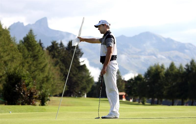CRANS, SWITZERLAND - SEPTEMBER 02:  Oliver Wilson of England tends the flag on the tenth hole during the Pro Am prior to the start of The Omega European Masters at Crans-Sur-Sierre Golf Club on September 2, 2009 in Crans Montana, Switzerland.  (Photo by Andrew Redington/Getty Images)