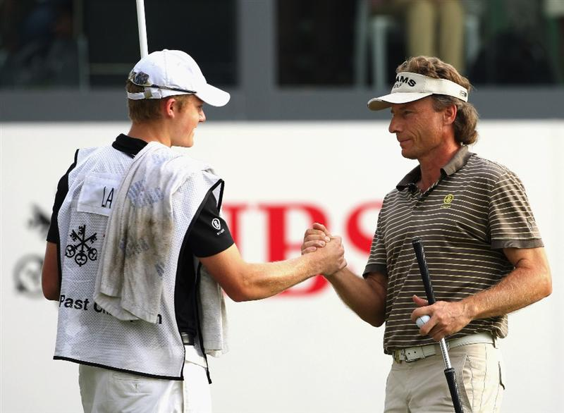 HONG KONG, CHINA - NOVEMBER 22:  Bernhard Langer of Germany shakes hands with his caddy, and son, Stefan Langer on the 18th hole during the third round of the UBS Hong Kong Open at the Hong Kong Golf Club on November 22, 2008 in Fanling, Hong Kong.  (Photo by Stuart Franklin/Getty Images)