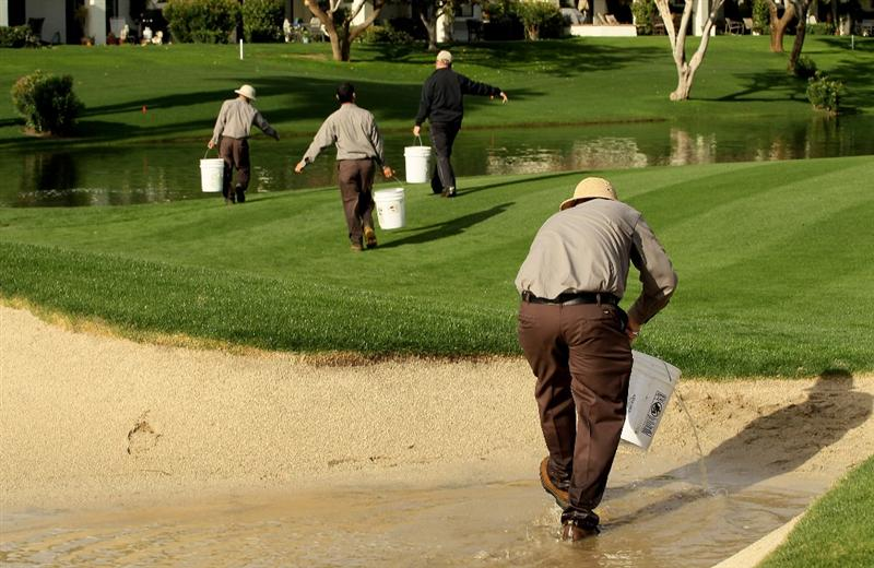 LA QUITNA, CA - JANUARY 22: Workers bail out a bunker on the Palmer Private Course at PGA West before the  delayed second round of the Bob Hope Classic on January 22, 2010 in La Quinta, California. (Photo by Stephen Dunn/Getty Images)
