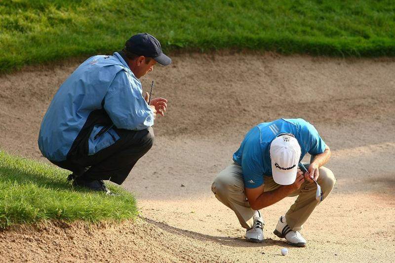 OAKVILLE, ONTARIO - JULY 24:  Martin Laird of Scotland looks at his ball placement with a rules official before the restart of play during round two of the RBC Canadian Open at Glen Abbey Golf Club on July 24, 2009 in Oakville, Ontario, Canada.  (Photo by Chris McGrath/Getty Images)