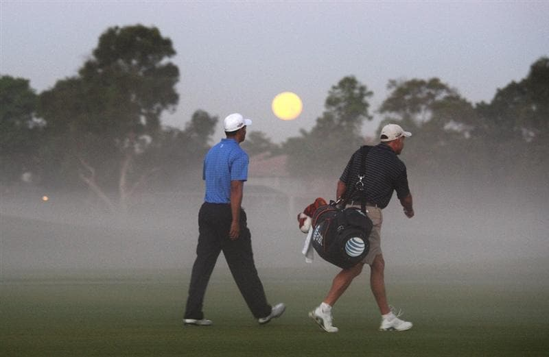 DORAL, FL - MARCH 11: Tiger Woods of the USA walks with his caddie Steve Williams of New Zealand  from the 1st tee as the moon dips below the trees during the final day of practice for the World Golf Championships-CA Championship at the Doral Golf Resort & Spa on March 11, 2009 in Miami, Florida  (Photo by David Cannon/Getty Images)