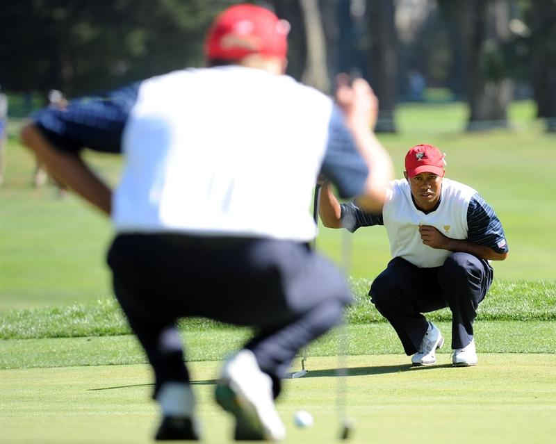 SAN FRANCISCO - OCTOBER 09:  Tiger Woods of the USA Team lines up a putt with Steve Stricker on the seventh hole during the Day Two Fourball Matches of The Presidents Cup at Harding Park Golf Course on October 9, 2009 in San Francisco, California.  (Photo by Harry How/Getty Images)