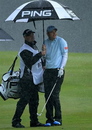 VIRGINIA WATER, ENGLAND - MAY 26:  Gary Boyd of England shelters with his caddie as the rain falls during the first round of the BMW PGA Championship at Wentworth Club on May 26, 2011 in Virginia Water, England.  (Photo by David Cannon/Getty Images)