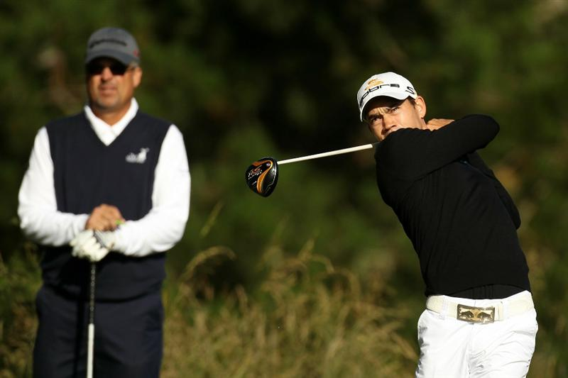 PEBBLE BEACH, CA - JUNE 16:  Camilo Villegas of Colombia (R) hits a tee shot as Kenny Perry looks on during a practice round prior to the start of the 110th U.S. Open at Pebble Beach Golf Links on June 16, 2010 in Pebble Beach, California.  (Photo by Ross Kinnaird/Getty Images)