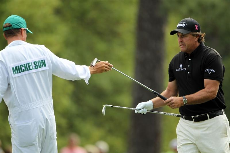 AUGUSTA, GA - APRIL 08:  Phil Mickelson swaps clubs with caddie Jim 'Bones' Mackay on the first hole during the second round of the 2011 Masters Tournament at Augusta National Golf Club on April 8, 2011 in Augusta, Georgia.  (Photo by Jamie Squire/Getty Images)