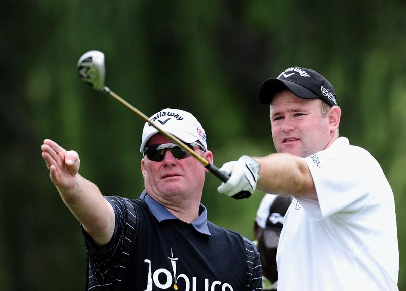 JOHANNESBURG, SOUTH AFRICA - JANUARY 14:  Alastair Forsyth of Scotland (R) and caddie discuss his tee shot during the first round of the Joburg Open at Royal Johannesburg and Kensington Golf Club on January 14, 2010 in Johannesburg, South Africa.  (Photo by Stuart Franklin/Getty Images)