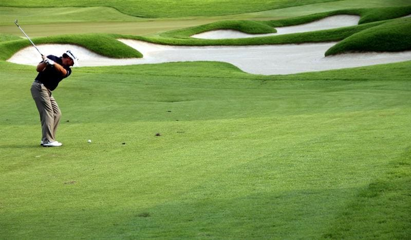 SINGAPORE - NOVEMBER 13 : Graeme Mcdowell of Northern Ireland hits his approaching shot on the 18th hole during the Third Round of the Barclays Singapore Open held at the Sentosa Golf Club on November 13, 2010 in Singapore, Singapore.  (Photo by : Stanley Chou/Getty Images)