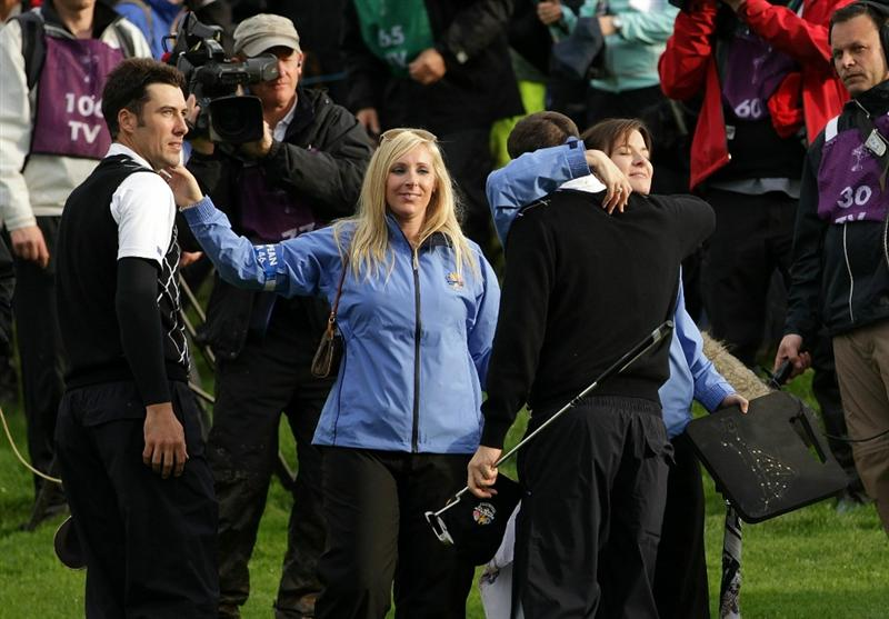 NEWPORT, WALES - OCTOBER 03:  Ross Fisher (L) of Europe celebrates with Caroline Harrington as Padraig Harring hugs Fisher's wife Jo after winning their match on the 17th green during the Fourball & Foursome Matches during the 2010 Ryder Cup at the Celtic Manor Resort on October 3, 2010 in Newport, Wales.  (Photo by Andrew Redington/Getty Images)