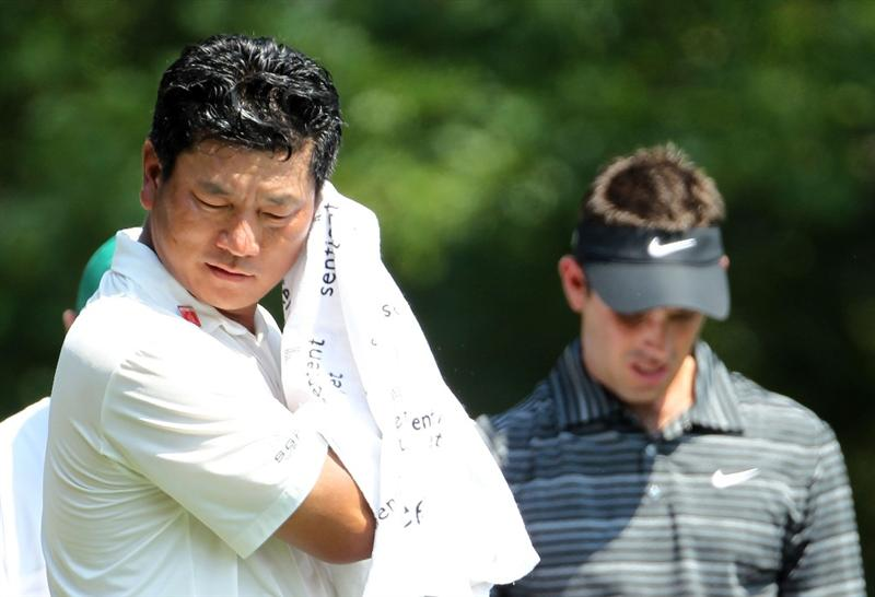 AUGUSTA, GA - APRIL 10:  K.J. Choi of South Korea wipes his face as Charl Schwartzel of South Africa looks on during the final round of the 2011 Masters Tournament at Augusta National Golf Club on April 10, 2011 in Augusta, Georgia.  (Photo by Jamie Squire/Getty Images)