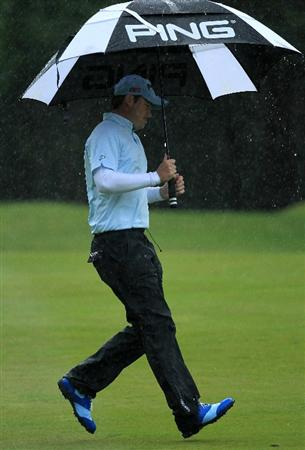 VIRGINIA WATER, ENGLAND - MAY 26:  Gary Boyd of England shelters under an umbrella as the rain falls during the first round of the BMW PGA Championship at Wentworth Club on May 26, 2011 in Virginia Water, England.  (Photo by David Cannon/Getty Images)
